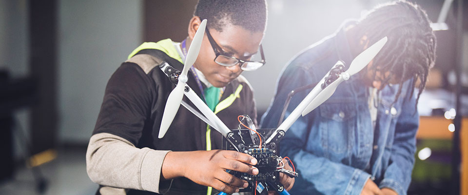 student in class working on a drone
